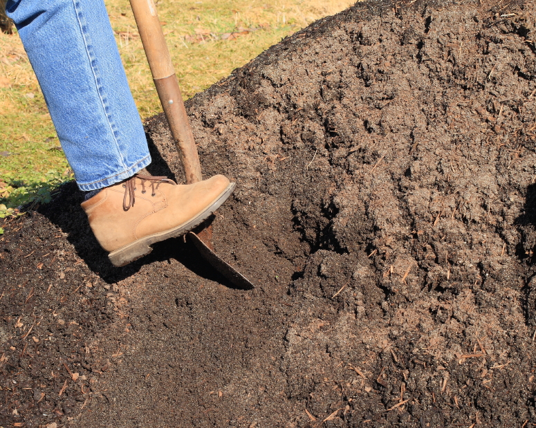 Person digging into a pile of topsoil